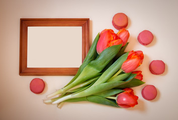 Blank picture frame, tulips and macaroons on pastel background