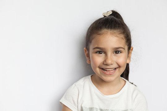 Portrait of happy cute brunette child  girl on white background