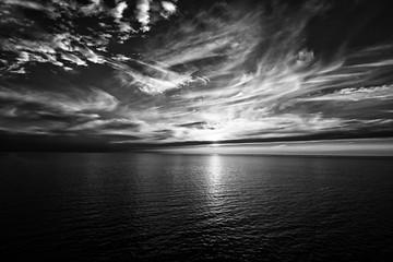 Sonnenuntergang am Horizont auf dem Meer, schwarz/weiss