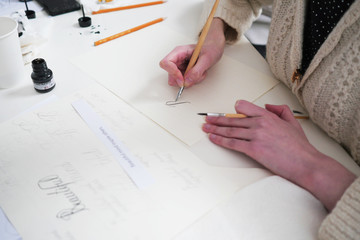 Calligraphy lettering workshop. Young women's hand, writting letters. Calligraphy sheets, nibs, paper, ink and pens
