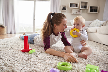 Young Mother Playing With Toddler Son On The Floor At Home