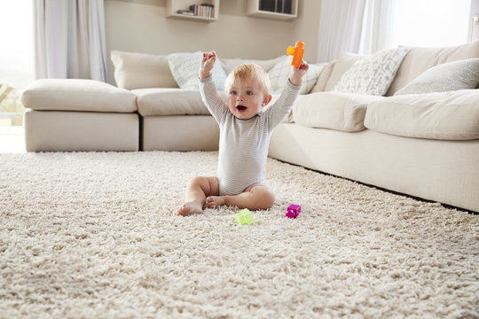 White toddler boy on the floor in sitting room raising arms