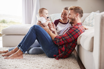 Young white couple play with their toddler in sitting room Wall mural