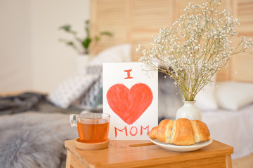 Mother's Morning breakfast on wooden tray near bed with greeting card I love you mom. Mother's Day concept.
