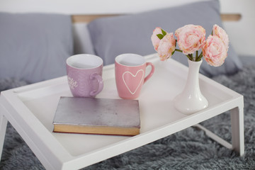 breakfast table in the bed. cup of tea in the morning in bed. pink cup with a heart