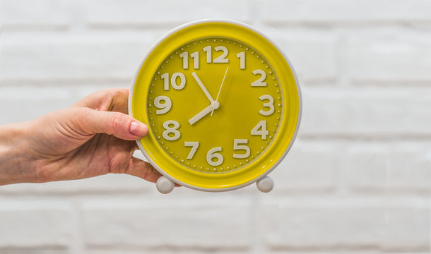 Yellow round clock in a female hand on a white background