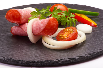 Tasty appetizer of thinly sliced spicy salami smoked sausage whith colorfull vegetabless on a stone rustic board isolated on white background