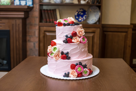 Three tiered pink wedding cake decorated with berries and flowers. Concept patisserie floristic from sugar mastic