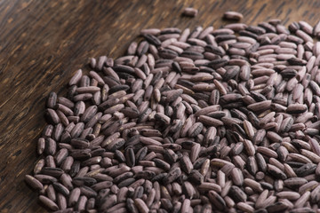 Dark purple rice on dark wooden background, top view, back-lit by sunlight