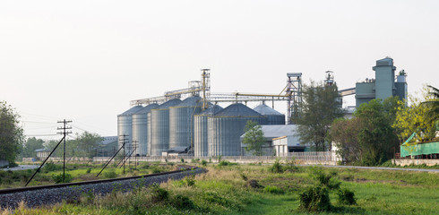 food industry building with agricultural silos and railway in the city