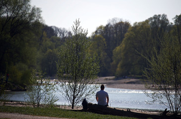People enjoy a sunny afternoon on the banks of the Isar river, downtown Munich