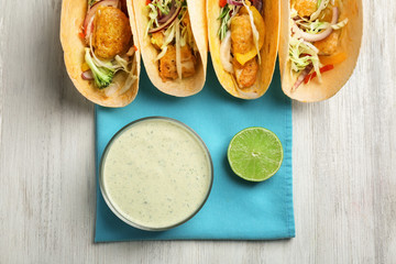 Tasty creamy lime sauce in bowl and fish tacos on wooden table