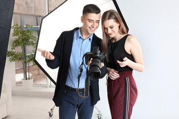 Photographer showing model her photos in professional studio