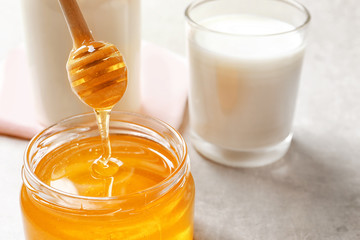 Honey pouring from dipper into jar on table