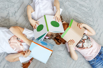 Three children of students with books. Preparation for exams. The concept of lifestyle, childhood, education, family, school.
