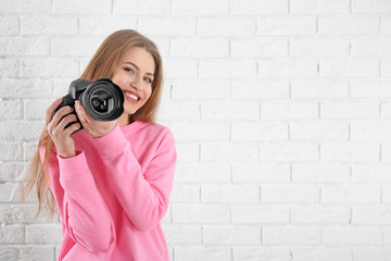 Female photographer with camera on brick background