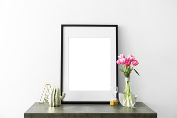 Mockup of blank frame and flowers on table