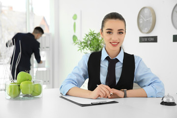 Busy female receptionist at workplace in hotel