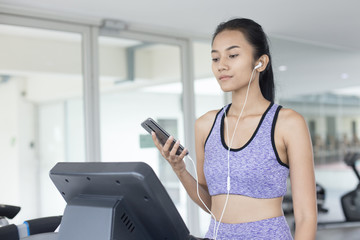 Woman listining song while exercise at fitness gym. Sport and Reaction concept.