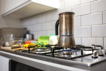 Coffee maker on the gas with fruit being prepared for breakfast in a white kitchen
