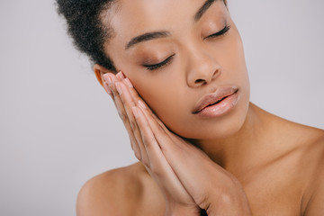 sensual african american woman with perfect skin leaning head on hands isolated on grey