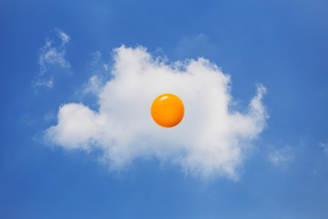 Yellow yolk with white cloud on blue sky. Food concept
