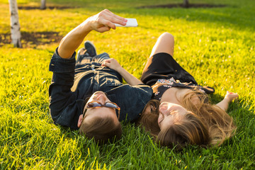 love and people concept - happy teenage couple lying on grass and taking selfie on smartphone at summer