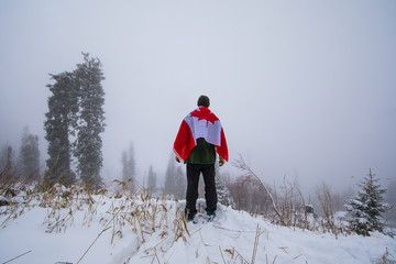 man traveler with the Canadian flag in the mountains