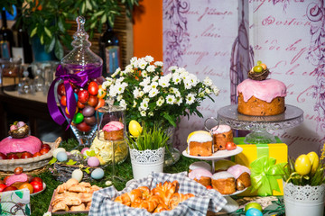 Easter table: cakes with colored glaze on stands, colored eggs and bouquets of flowers