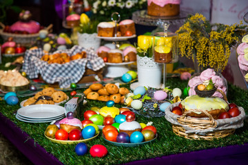 Multicolored eggs in wicker baskets and buns