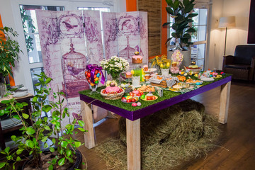 a wooden table with a grassy tablecloth and Easter treats: eggs, cakes, chocolate eggs, meringues