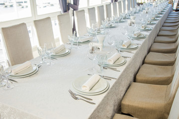 A long table covered with a white tablecloth with cutlery and glasses