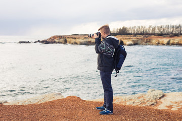 Young photographer with backpack making photos of sea and rocks with the camera. Mediterranean sea