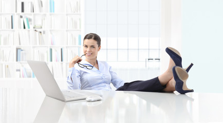 satisfied business smiling woman in office with computer and feet on desk, career and success concept