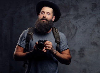Portrait of a handsome bearded traveler in a hat with a backpack and tattooed arms, holds a photo camera, isolated on a dark background.