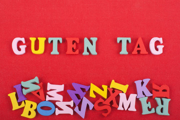 GUTEN TAG word on red background composed from colorful abc alphabet block wooden letters, copy space for ad text. Learning english concept.
