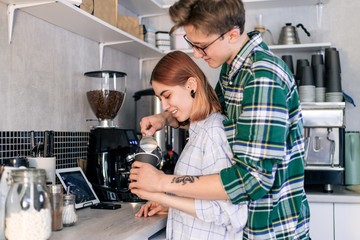 Loving couple of young people preparing coffee in the kitchen