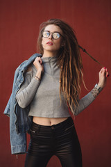 Stylish woman with dreadlocks posing against red wall background
