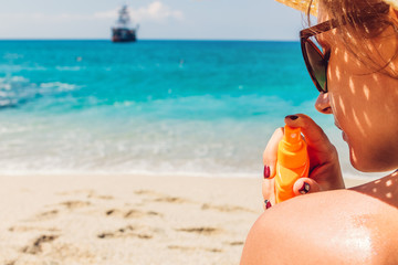 Sun cream protection. Woman sprays sun cream on shoulder. Skin care concept. Healthy skin on vacation.
