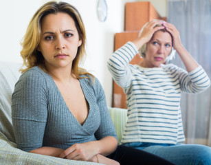 Mature mother and adult daughter quarrelling in domestic interior