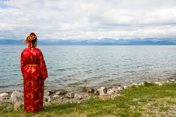 Woman in national clothes  looks at the lake Hovsgol, Mongolia