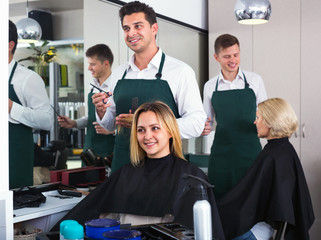 Cheerful man cutting long hair of girl