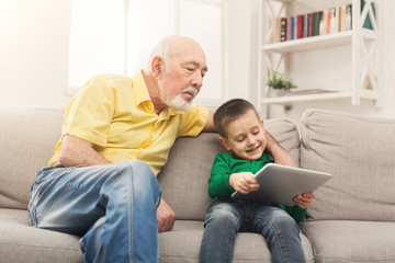 Senior man watching videos on tablet with grandson
