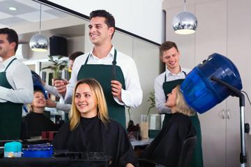 Smiling young man cutting long hair of girl
