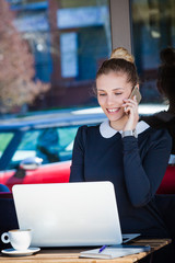 smiling  woman student or business sit in cafe outdoor use smart phone and  laptop