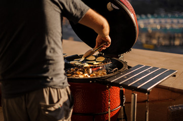 Man cooking peppers, mushrooms and egg-plants on the grill