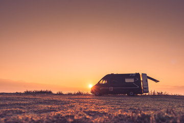 Camper car on nature at sunrise