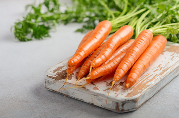 Bunch of fresh carrots on wooden cutting board, selective focus.