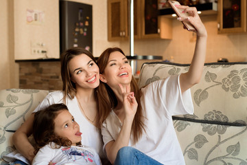 Selfie portrait of two young girls and little girl on the sofa at home.
