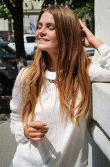 Portrait of young beautiful woman with long hair dressed in white blouse staying outside closed her eyes, smiling.
